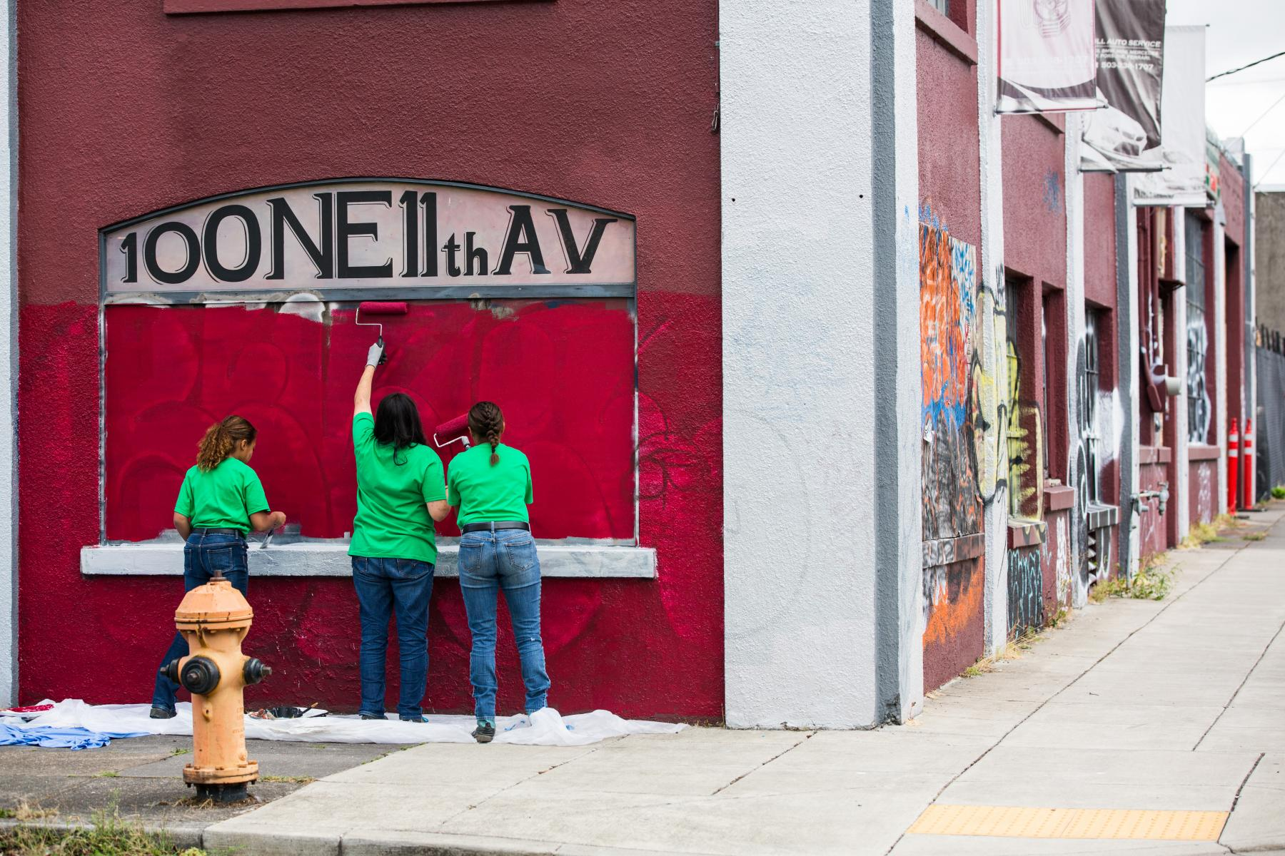 three teens painting the side of an old building
