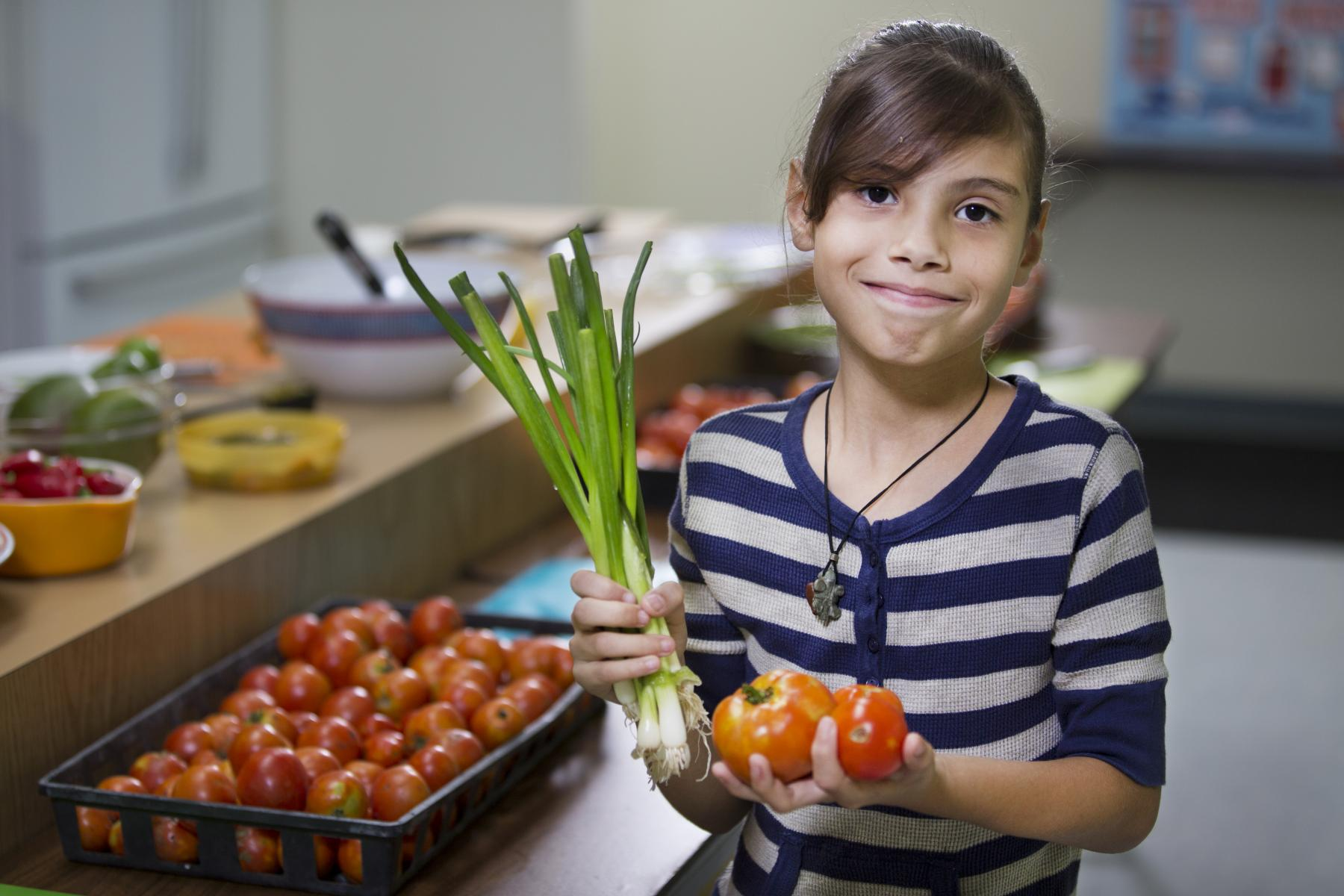 child showing off fresh fruits and vegetables
