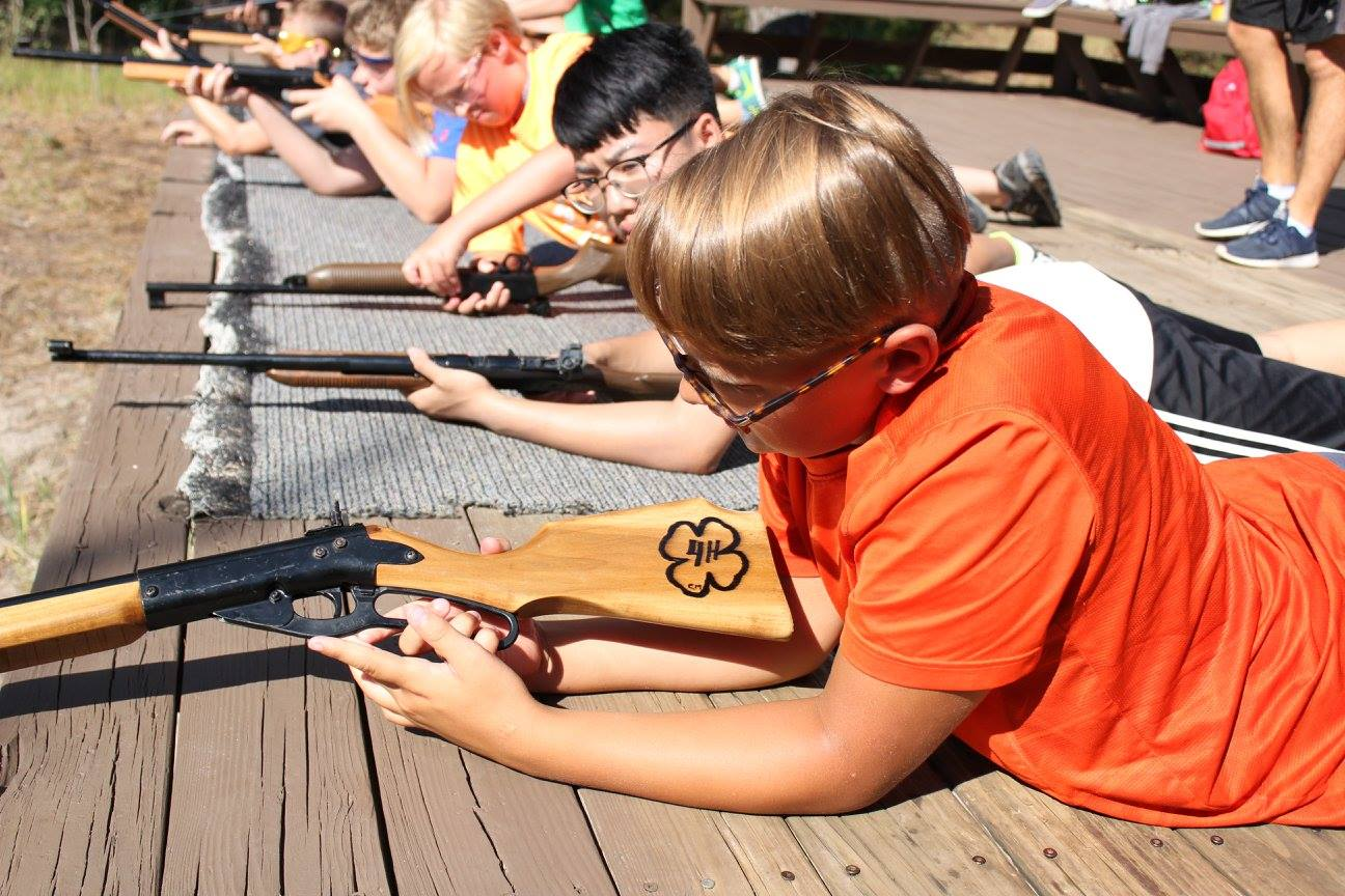 boy participating in camp shooting sports activity