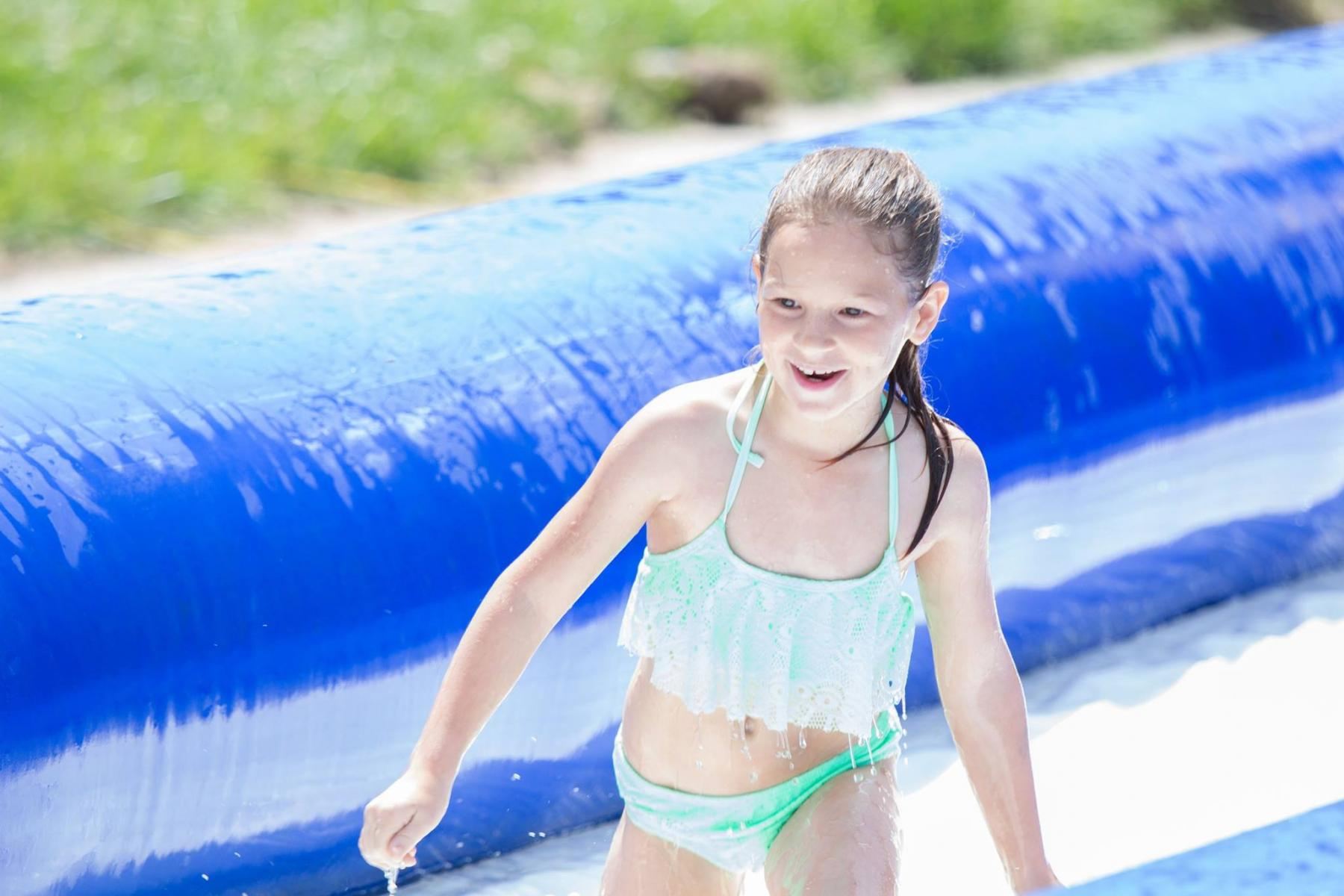 girl smiling at the bottom of a large waterslide