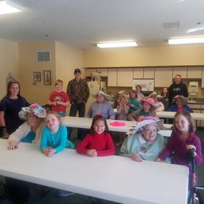 retirement home residents pose with their handcrafted bonnets alongside the Happy Hustlers 4-H Club members