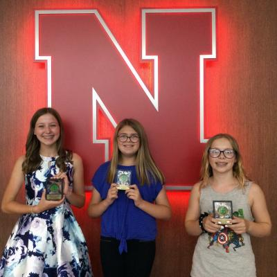 three 4-H members stand with their awards in front of glowing Nebraska N