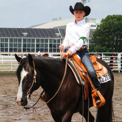4-H member riding horse in arena