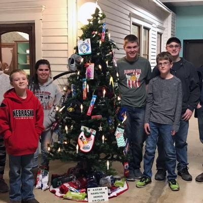 4 Star Hamilton Heroes 4-H Club members stand next to holiday tree