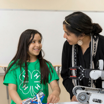 young girl wearing a 4-H t-shirt smiles as an adult judge talks to her