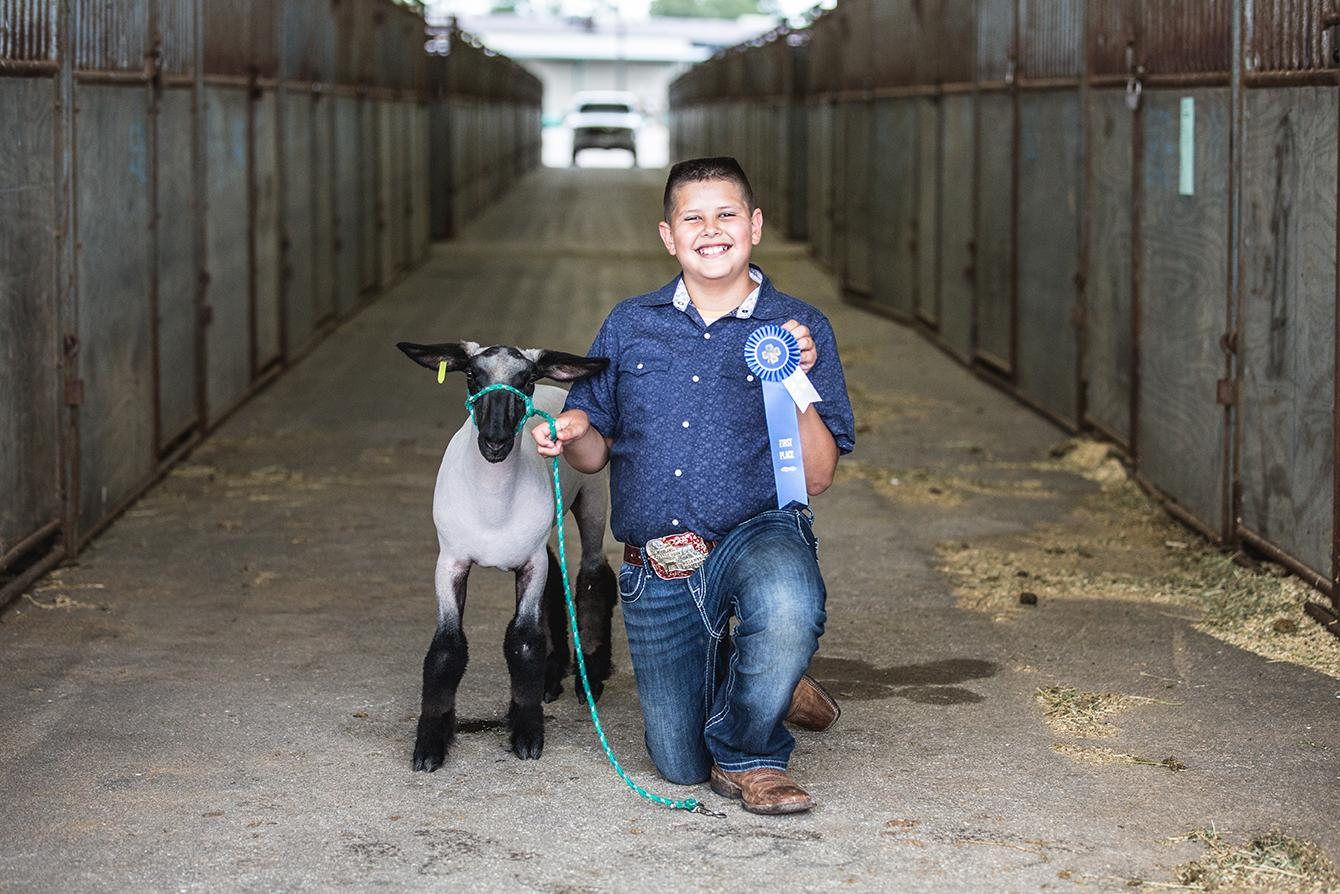 smiling 4-H'er shows off their blue ribbon and their show lamb