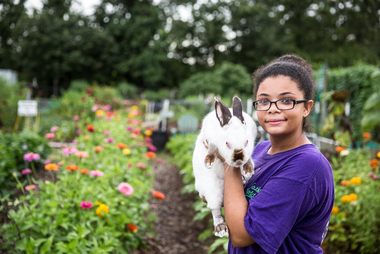 teen standing in garden holding pet rabbit