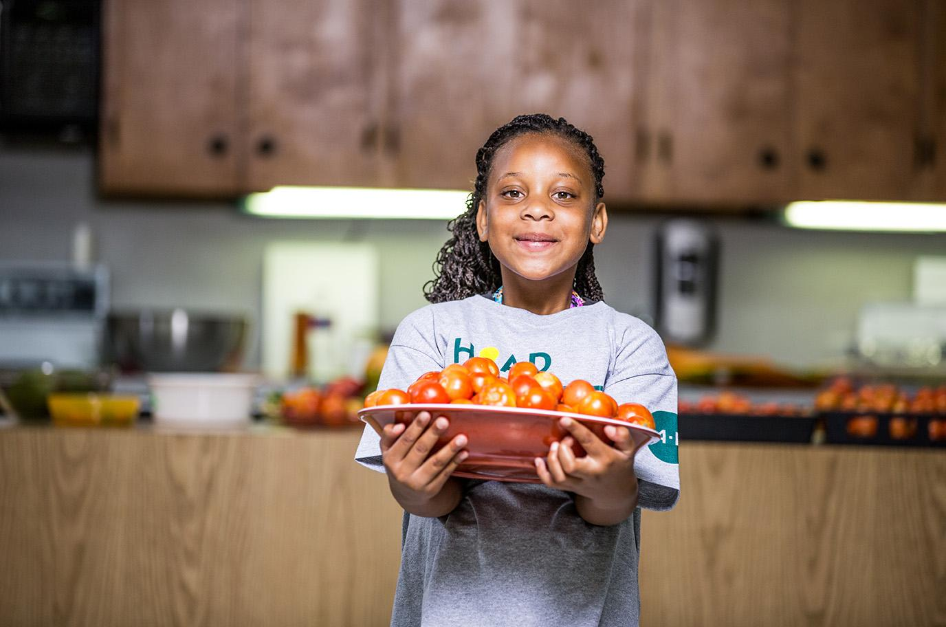 child carrying plate of vegetables