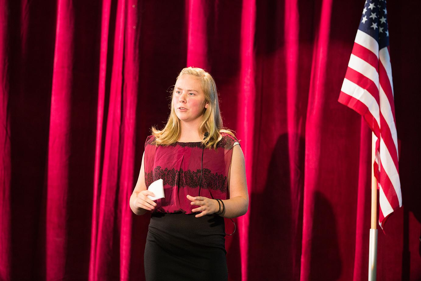teen girl giving a speech on stage