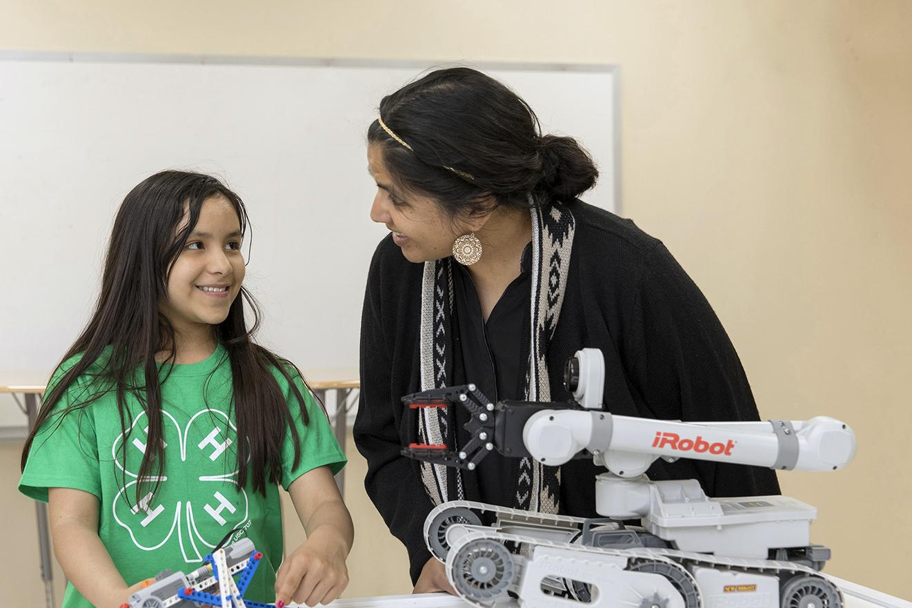 adult talking to youth about her robotics project that is sitting in front of them