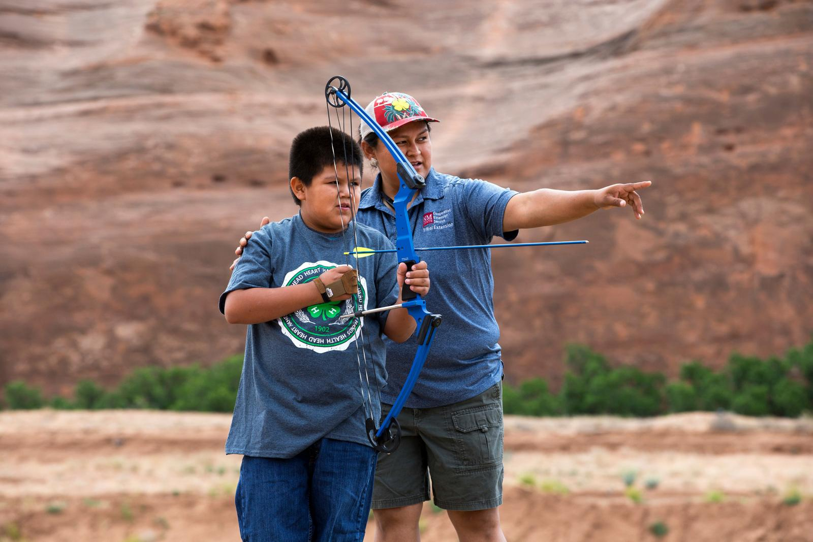 4-H volunteer helping youth with archery