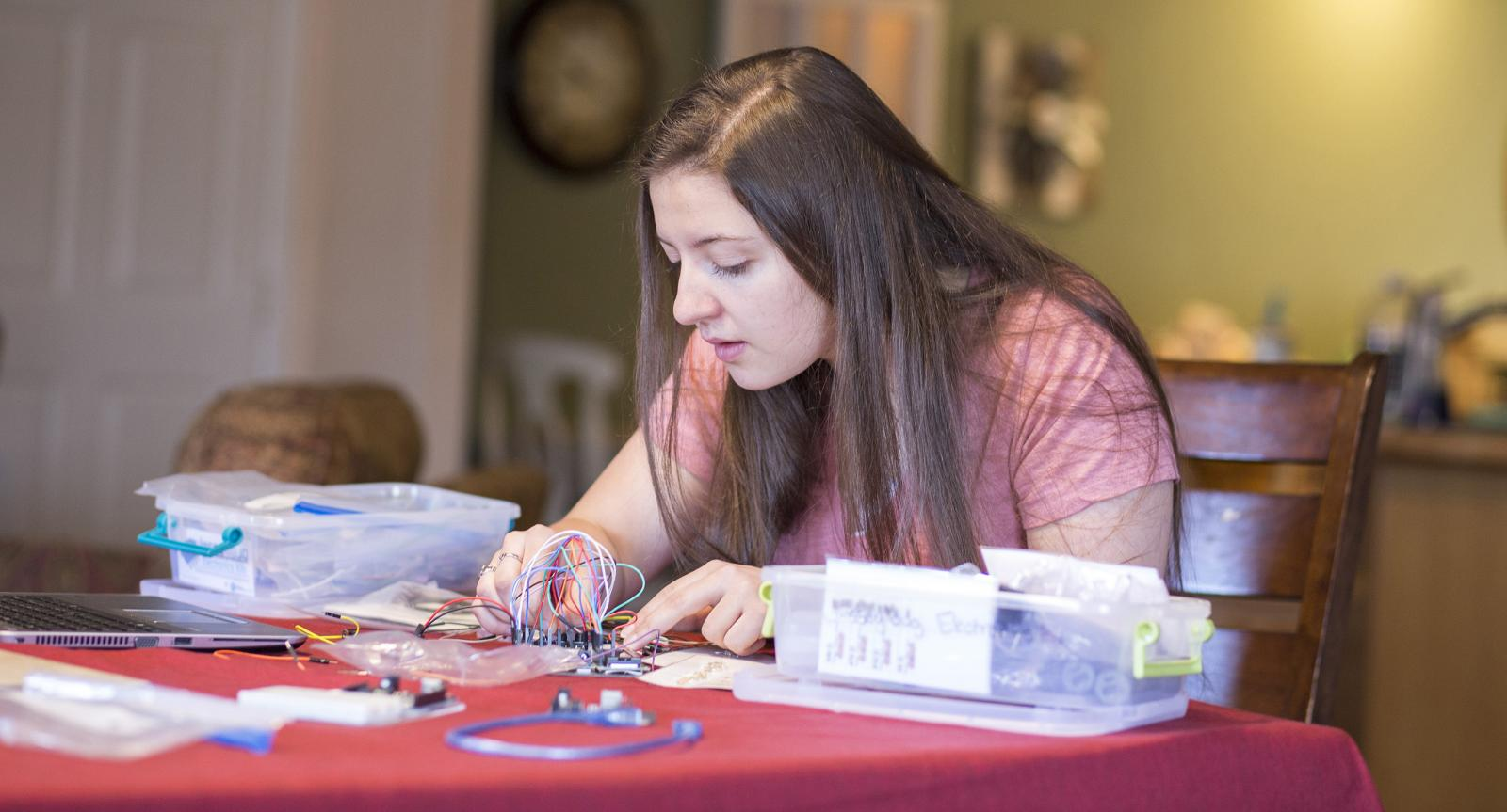 teen sits at kitchen table working on robotics project