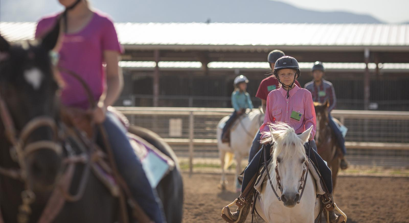 young people riding horses calmly around an arena