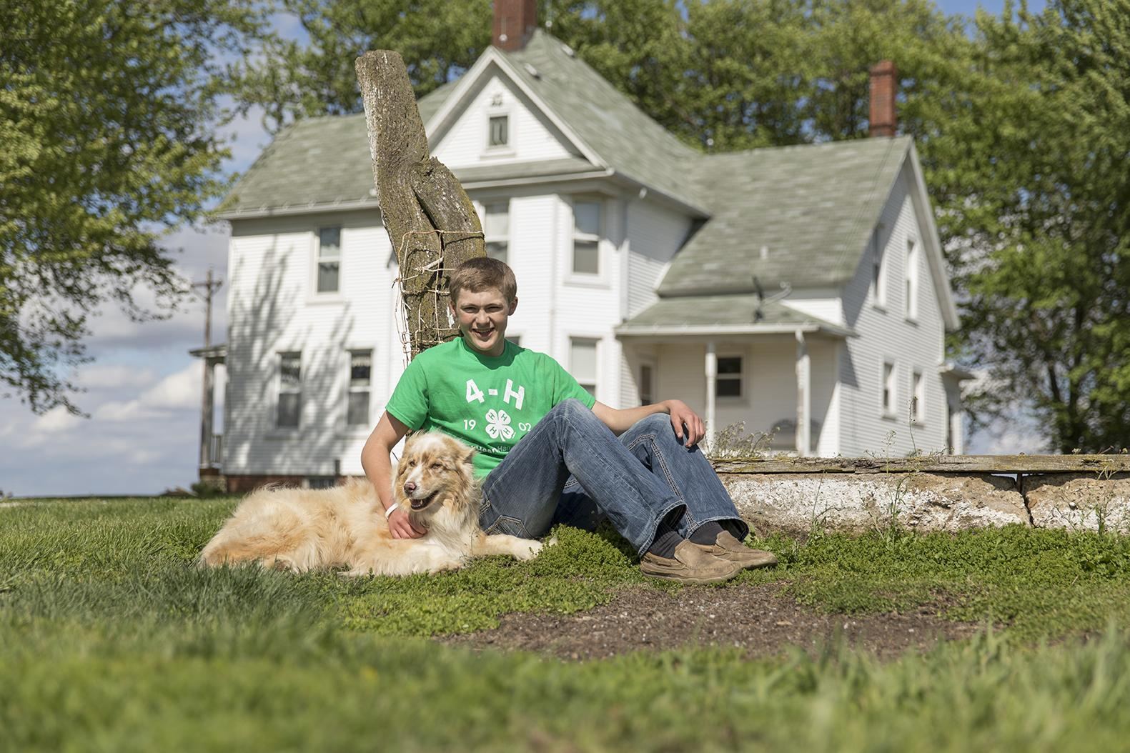 4-H'er sitting with his dog