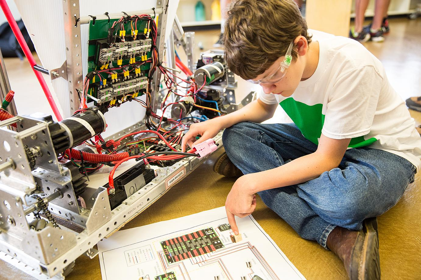 child reads instructions while putting together large robot