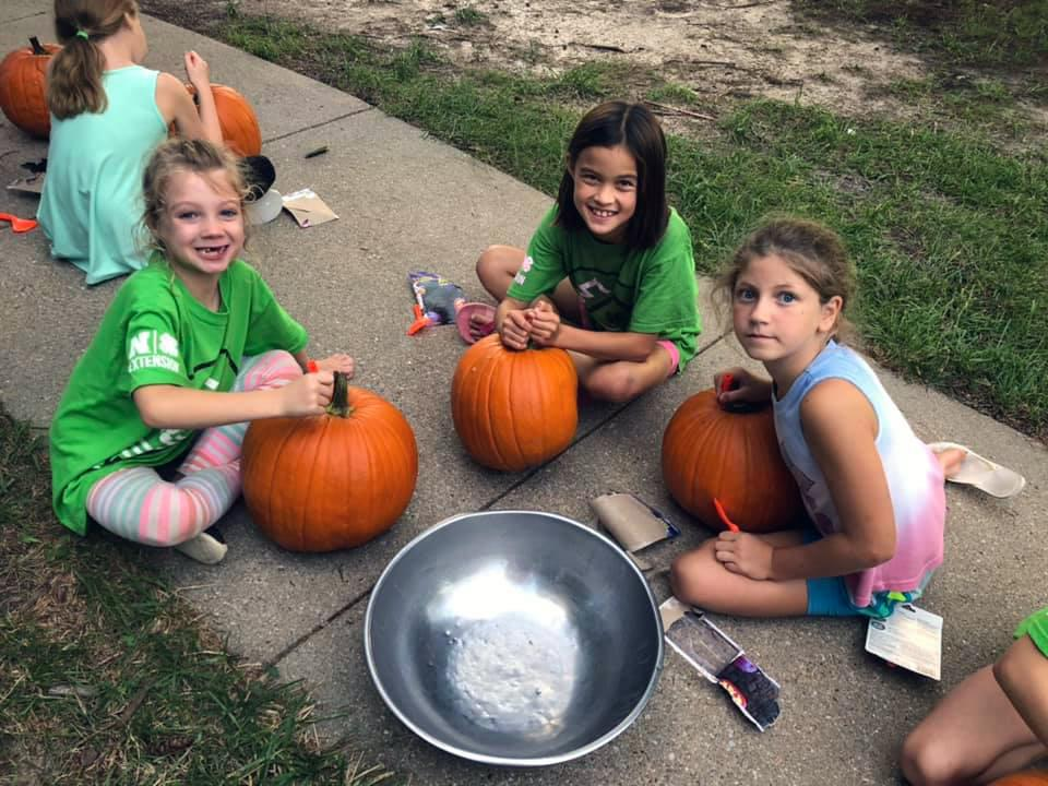 girls carving jack-o-lanterns