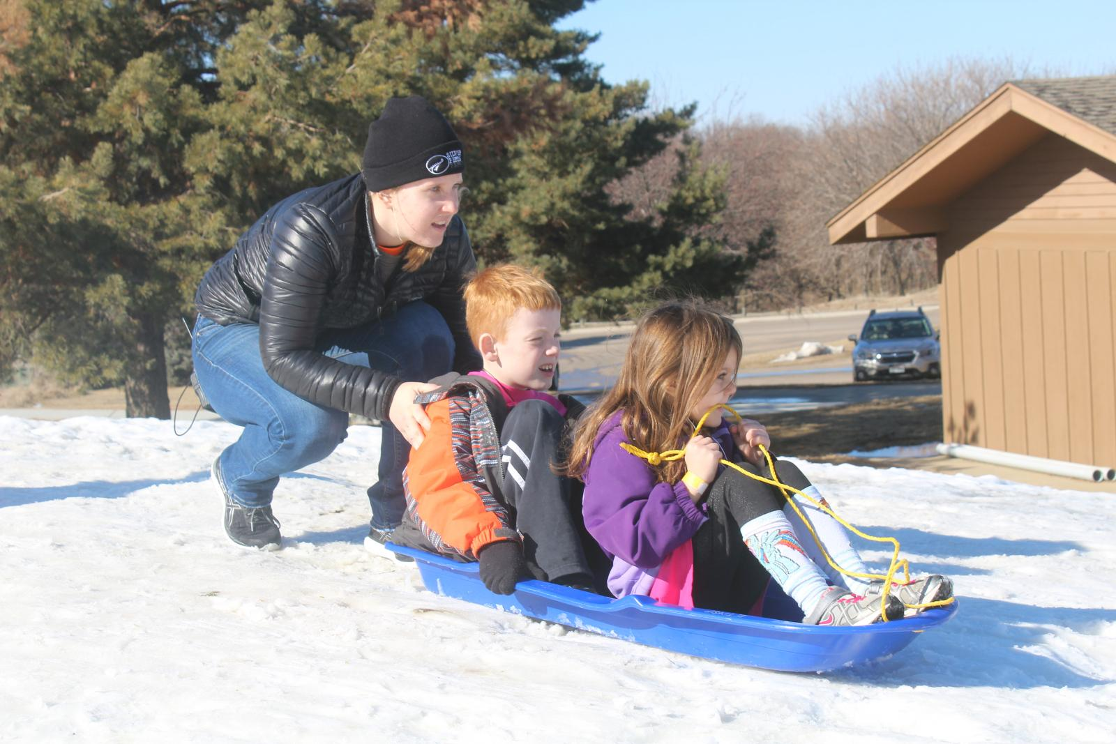 kids sledding down a snow covered hill