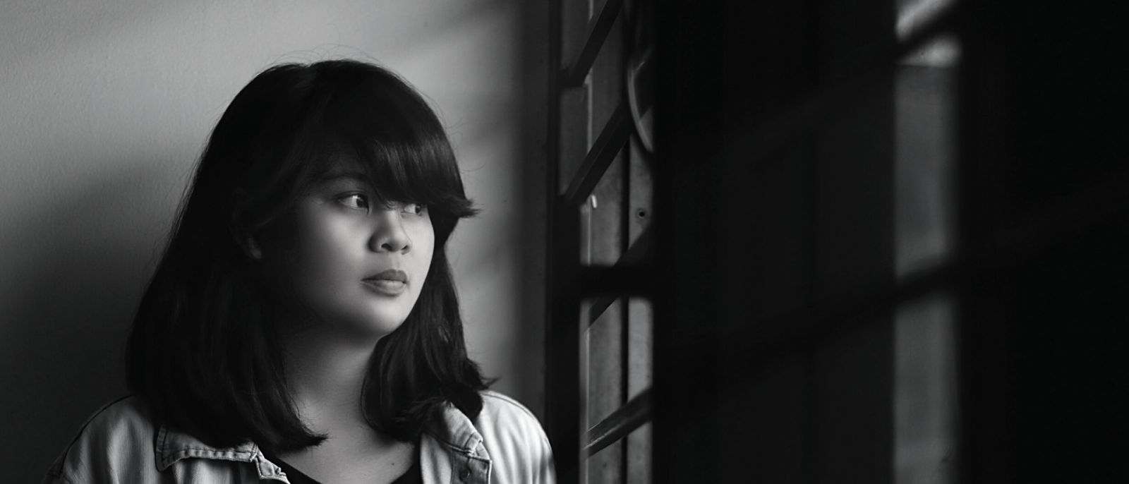 black and white photo of teen girl staring out a window