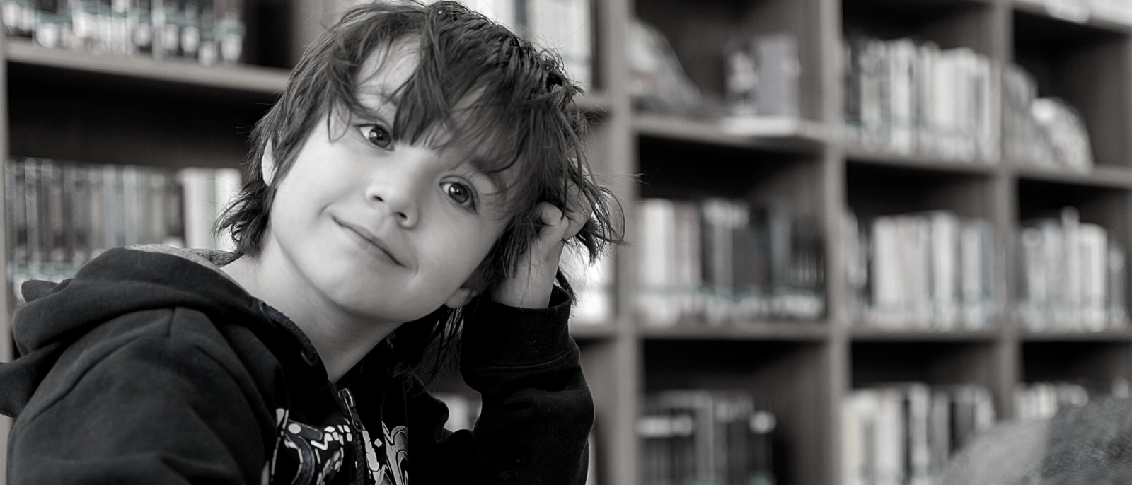 black and white photo of young boy scratching his head in thought