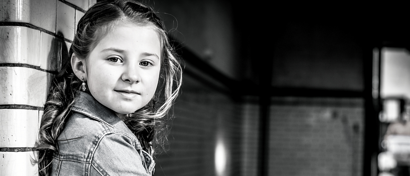 black and white photo of young girl leaning against a brick wall