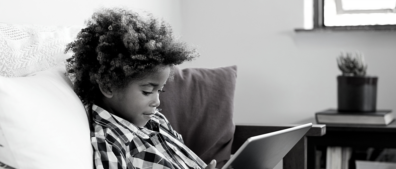 black and white photo of young boy looking down at a tablet
