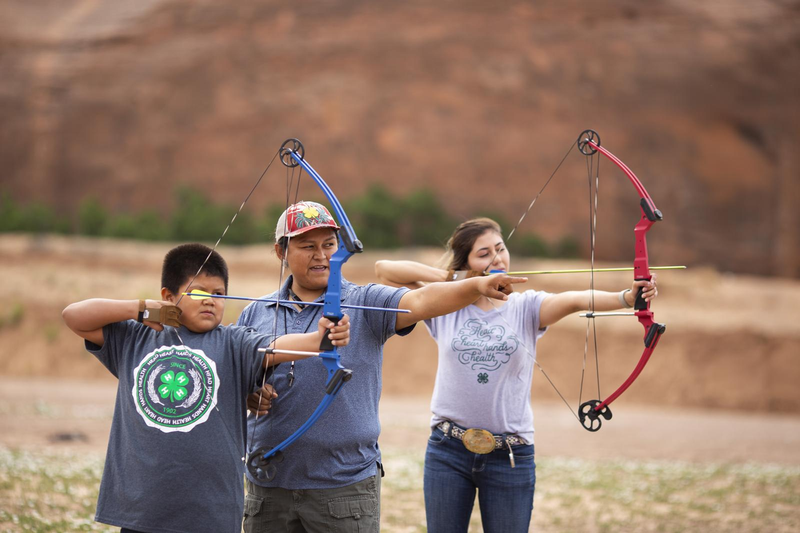 4-H volunteer teaching kids archery