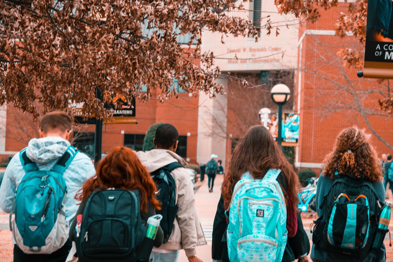 students wearing backpacks walking across campus
