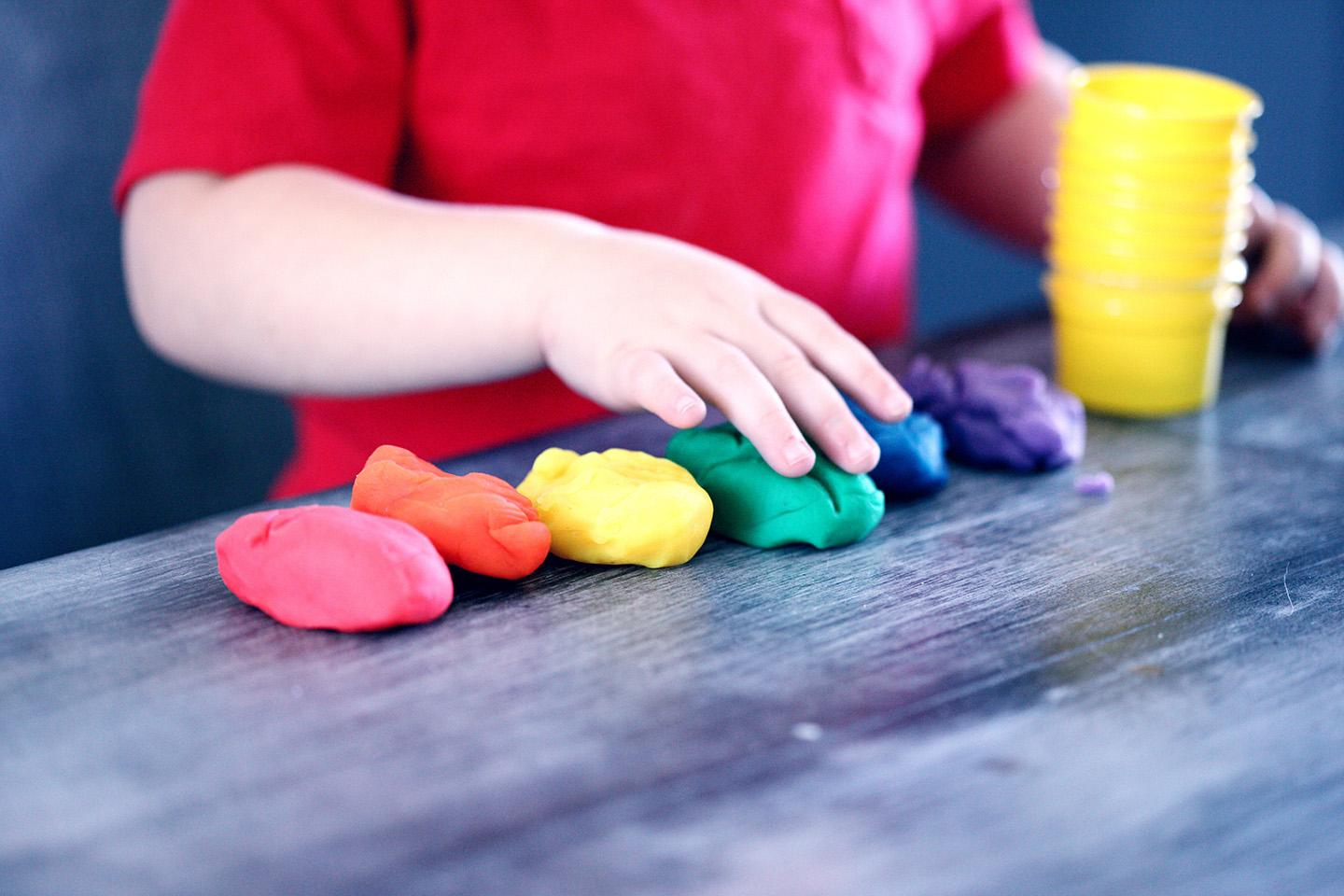 young child organizes balls of playdough by color