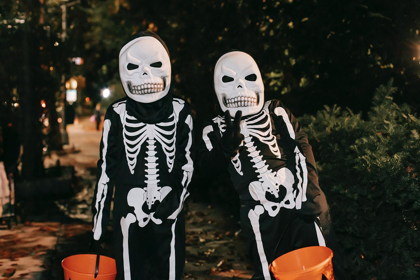two children dressed up as skeletons for Halloween pose for a photo